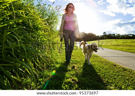 Young woman and golden retriever walking in the grass - stock photo