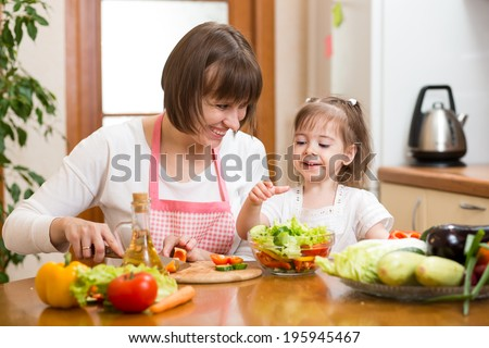 Young woman and her child daughter making vegetable salad - stock photo