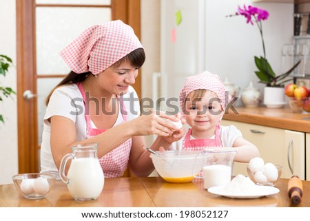 Young woman and her daughter cooking together at home - stock photo