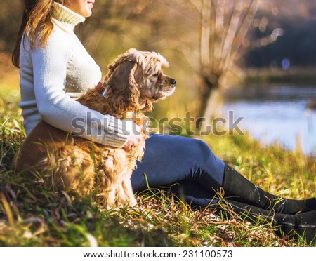 Young woman and her dog (American Cocker Spaniel) posing in park near lake  - stock photo