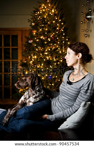 Young woman and her dog watching television at Christmas time - stock photo
