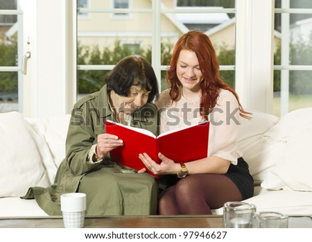 Young woman and her Grandmother looking in the Photo Album - stock photo