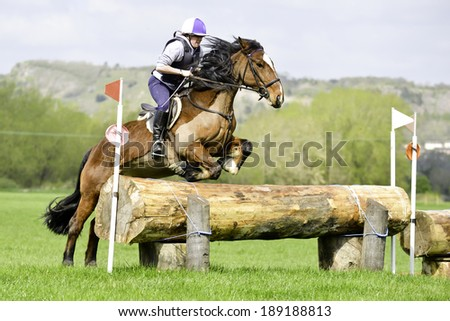 Young woman and her horse jumping log on cross country course at equine event - stock photo