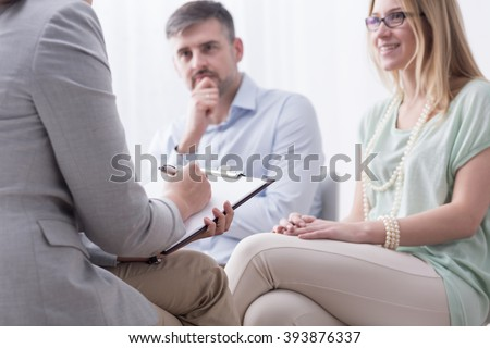 Young woman and her husband taking advice at psychiatrist - stock photo