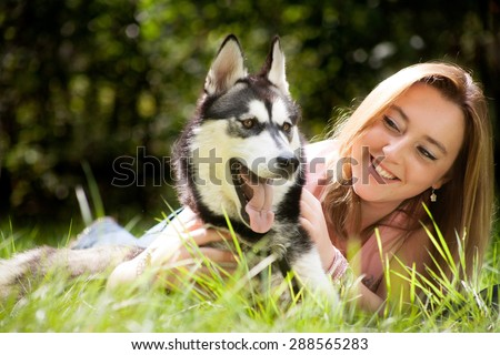 Young woman and her husky in the forest - stock photo
