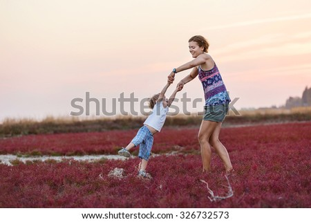 Young woman and her son having fun outdoors - stock photo
