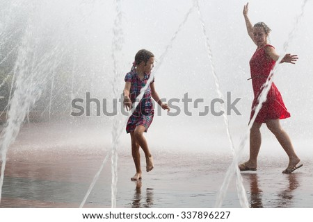 Young woman and little girl are dancing into the fountain. - stock photo