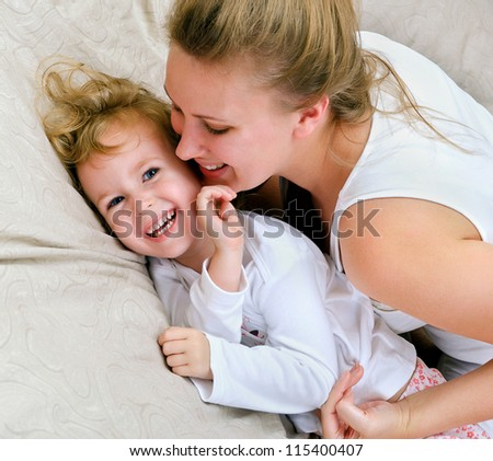 Young woman and little girl having fun in bed - stock photo