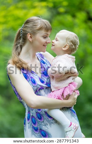 Young woman and little girl in the park. Mother with her charming daughter looking at each other on open air - stock photo