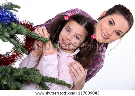 Young woman and little girl near a Christmas tree - stock photo