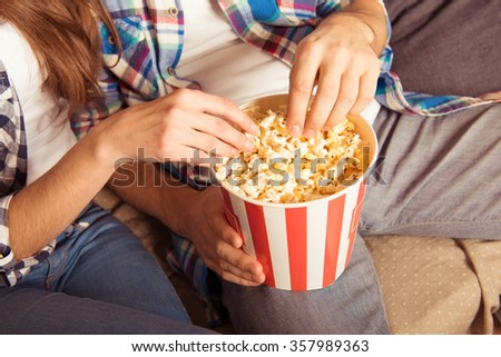 young woman and man in tartan shirt eating popcorn - stock photo