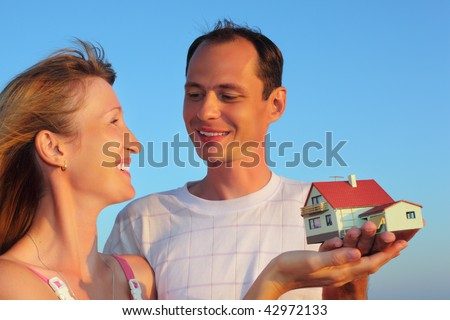Young woman and man keeping in hands model of house with garage against sky in summer - stock photo