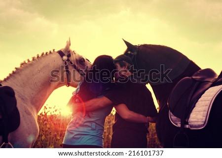 young woman and man kiss and hug and riding at horses - stock photo
