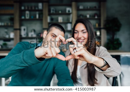 Young woman and man making heart shape with hands - stock photo
