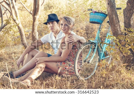 Young woman and man with retro bicycle sitting on a grass in a park - outdoor portrait - stock photo