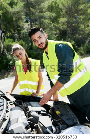 young woman and mechanic assistance on roadside with car breakdown - stock photo