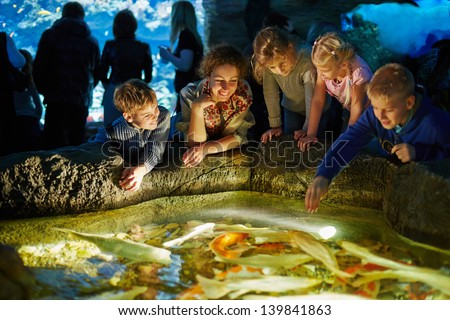 Young woman and several children see after fishes in enlighted pool at oceanarium - stock photo