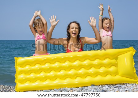 young woman and two little girls standing behind an inflatable mattress on beach, lifted hands upwards - stock photo