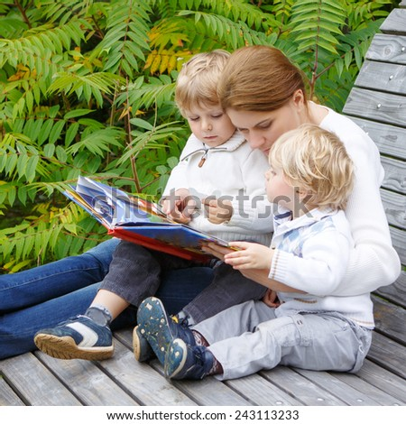 Young woman and two little sibling boys sitting on bench in park and reading fairytale book together. Family having fun and enjoying time together. Kid learning and development concept. - stock photo