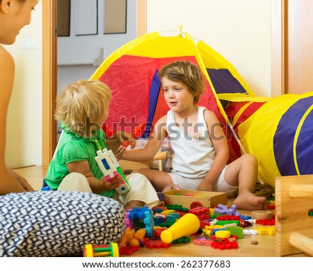 Young woman and two siblings together playing with  toys indoor - stock photo