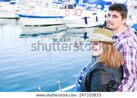 Young woman and young man on marina - stock photo