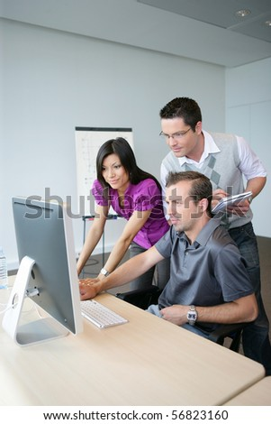 Young woman and young men in front of a desktop computer - stock photo