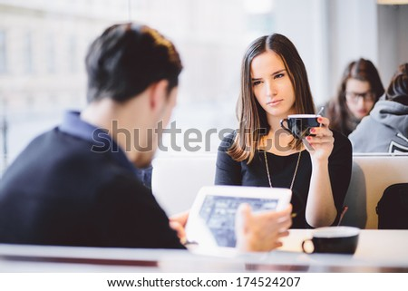 Young woman angry with boyfriend boyfriend for using tablet computer in cafe - stock photo