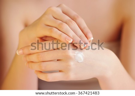Young woman applies cream on her hands after bath. Focus on hands - stock photo