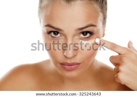 young woman apply concealer under the eye - stock photo