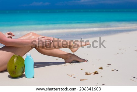 Young woman apply cream on her smooth tanned legs at tropical beach - stock photo