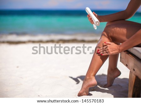 young woman apply cream on her smooth tanned legs on tropical beac - stock photo