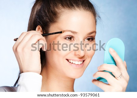 young woman apply shadow on eyebrows with brush, hold small mirror in other  hand, studio shot - stock photo