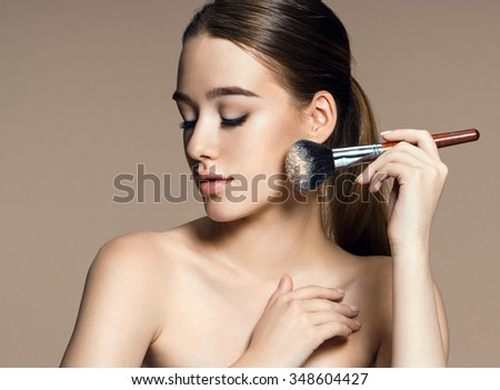 Young woman applying blusher on her face with powder brush, skin care concept / photo composition of brunette girl - on beige background - stock photo