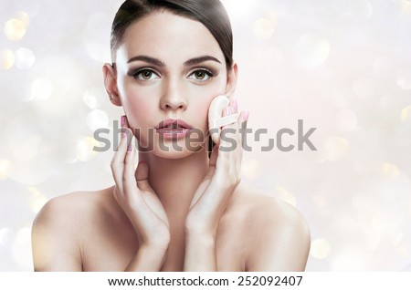 Young woman applying blusher on her face with powder puff, skin care concept / photoset of attractive brunette girl on blurred background with bokeh  - stock photo