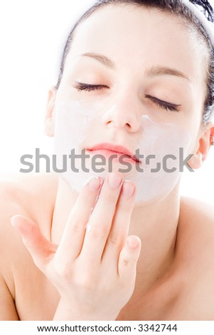 young woman applying creme on face - stock photo