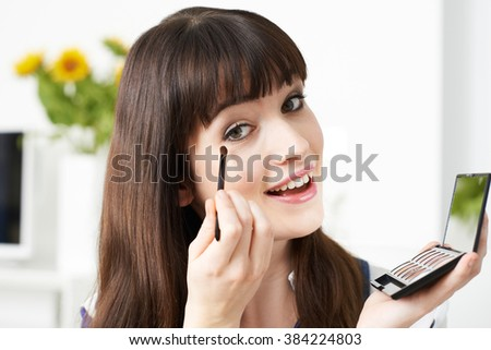 Young Woman Applying Eye Make Up At Home - stock photo