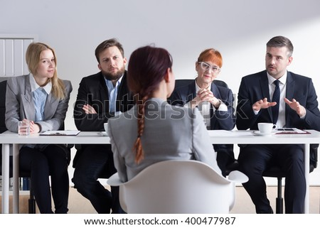 Young woman applying for a job in corporation. Talking in front of big commission - stock photo