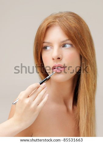 young woman applying lipstick with brush - stock photo