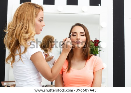 Young woman applying makeup to model in salon - stock photo