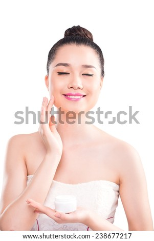 Young woman applying moisturizer on her face - stock photo