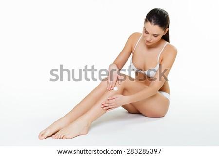 Young woman applying moisturizer on legs - stock photo