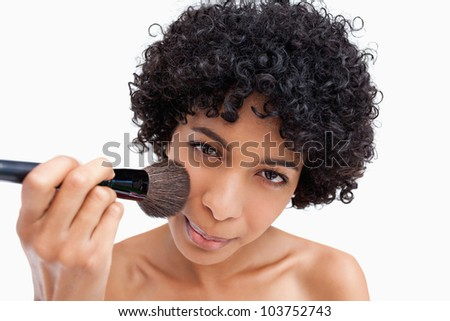 Young woman applying natural blush on her face with her powder brush - stock photo