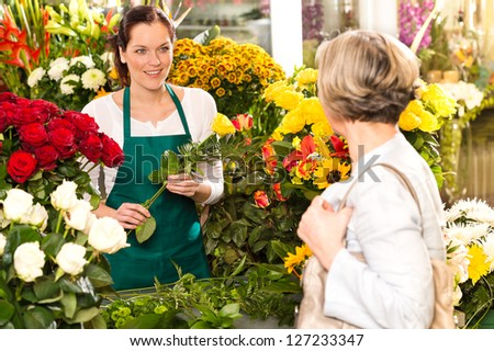 Young woman arranging flowers shop market selling customer smiling - stock photo