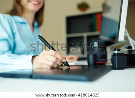 Young woman artist drawing something on graphic tablet at the home office - stock photo