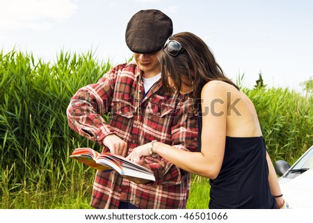 Young woman asking a farmer for advice on where to go, consulting a guide book - stock photo
