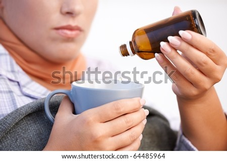 Young woman at home having flu, feeling bad, taking medicine, vitamin, drinking hot tea in bed.? - stock photo