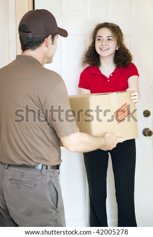 Young woman at home receives a package from a delivery man. - stock photo