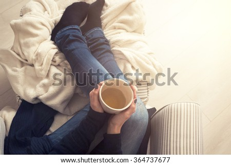 Young woman at home sitting in comfy armchair and drinking tea, view from above - stock photo