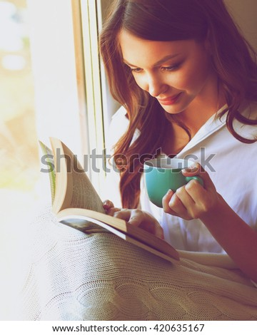 Young woman at home sitting near window relaxing in her living room reading book and drinking coffee or tea - stock photo