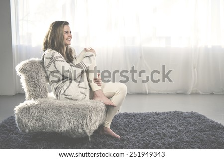 Young woman at home sitting on modern chair in front of window relaxing in her living room.  Instagram style  - stock photo